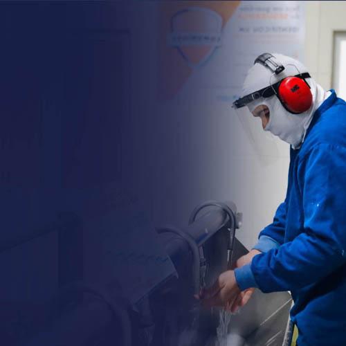 colaborador com equipamentos de proteção ao virus do covid-19 lavando as mãos